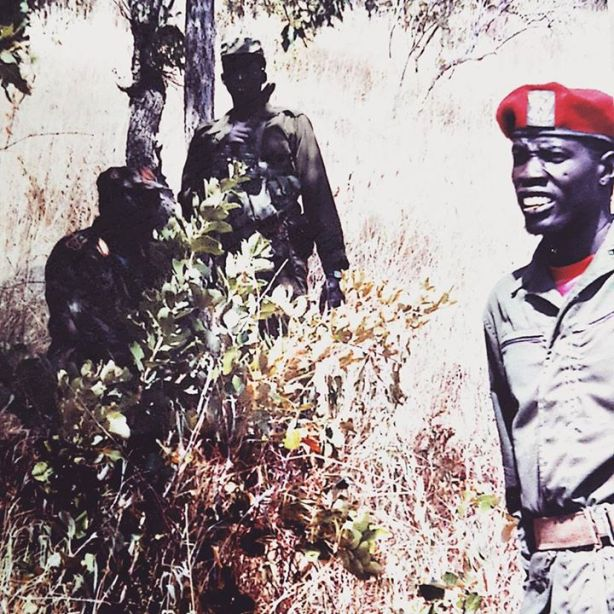 ...the late Luol Chol...valiant revolutionary singer of Koriom Division...with Garang'e Mabior in the background under under the tree...with Kuol Majak standing guard